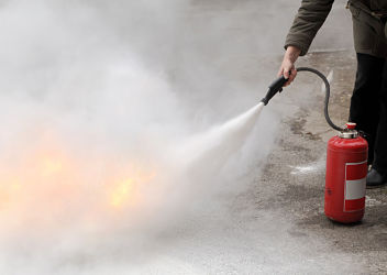 A woman demonstrating how to use a fire extinguisher