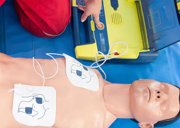 Paramedic activating portable defibrillator connected to CPR dummy during resuscitation training. Focus on CPR dummy